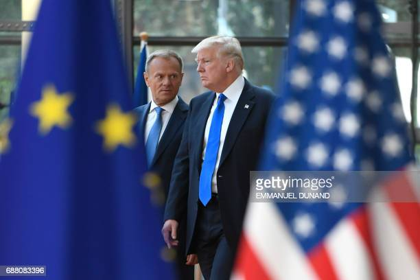 European Council President Donald Tusk speaks to US President Donald Trump as he welcomes him at EU headquarters as part of the NATO meeting in...