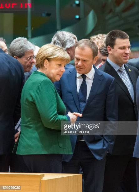 European Council President Donald Tusk talks with German Chancellor Angela Merkel on the second day of a European Summit at the Europa Building at...