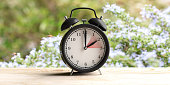 European daylight saving time end. Alarm clock on wooden desk, blur spring nature background, copy space. 3d illustration