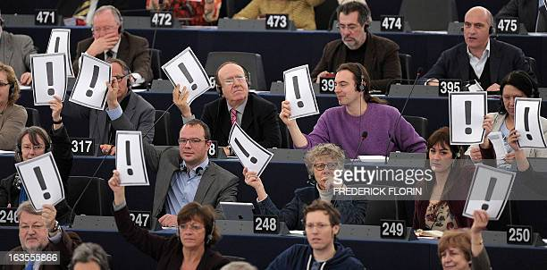 European Deputies hold on march 12 2013 placards bearing an exclamation mark during a session at the European Parliament in Strasbourg eastern France...
