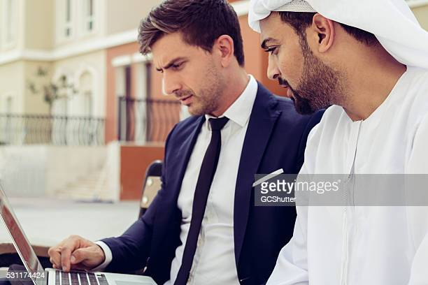 European Executive showing Arab Businessman Project Plan