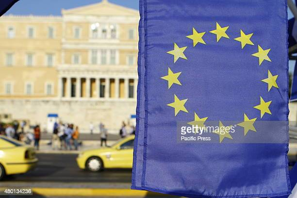 European flag is pictured with the Greek Parliament in the background Thousands of Greeks protested outside the Greek Parliament against a possible...