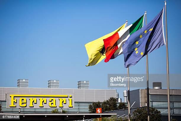 A European flag right an Italian flag centre and a Ferrari SpA flag fly above the entrance to the Ferrari SpA factory in Maranello Italy on Tuesday...