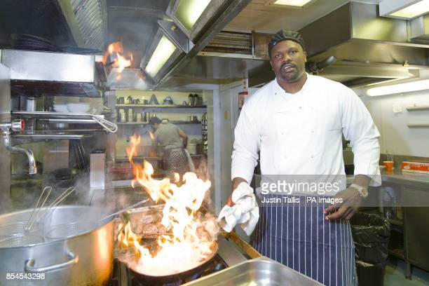 European Heavyweight Champion Dereck Chisora puts rabbit into a frying pan as part of his 'Recipe For Success' at Frederick's Restaurant in North...