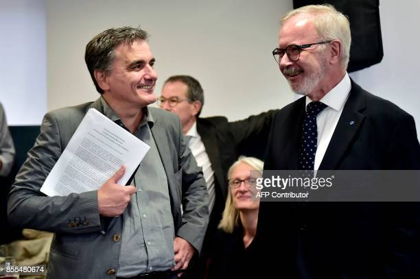 European Investment Bank President Werner Hoyer speaks with Greek finance minister Euclid Tsakalotos during the inauguration of the EIB offices in...