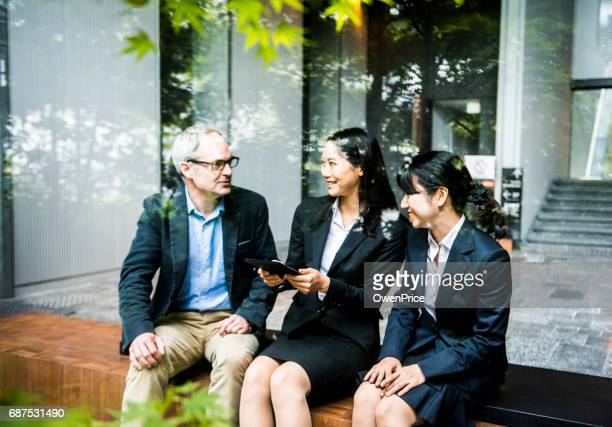 European man discussing concept with female Japanese team