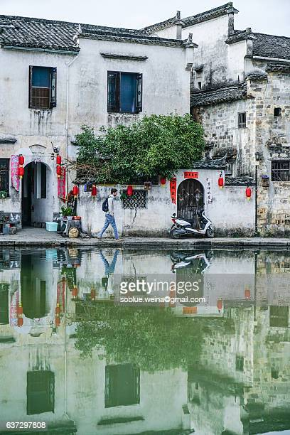 A european man tourist travelling Hongcun village UNESCO site  in China with Backpack.