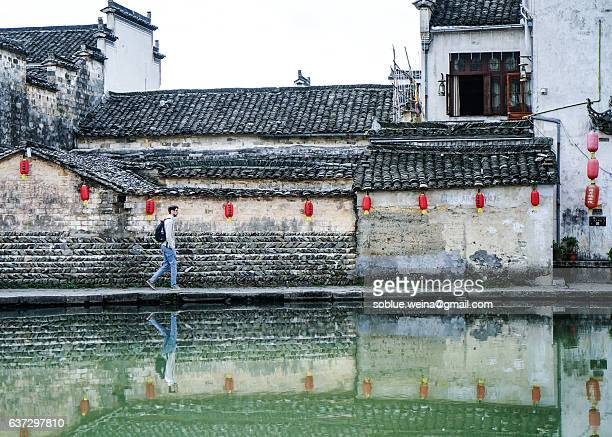 A european man tourist travelling Hongcun village UNESCO site  in China with Backpack. Walking along the pond.