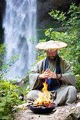 European man with beard and japanese robe makes fire ceremony in front of Great Waterfall in Gallizien in Austria