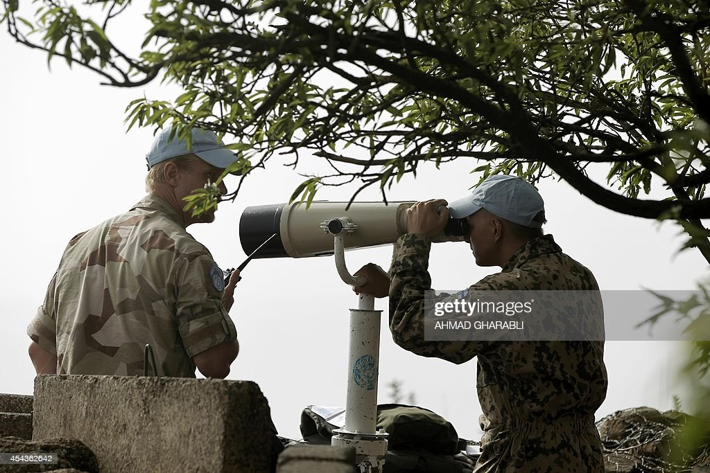 European members of United Nations Disengagement Observer Force (UNDOF) use binoculars to watch the Syrian side of the Golan Heights on August 30, 2014 in the Israeli-occupied Golan Heights, after Syrian rebel fighters took control of the Quneitra checkpoint between Israel and Syria. Philippine UN peacekeepers in the Golan Heights clashed with Syrian rebels , Defence Minister Voltaire Gazmin said in Manila.