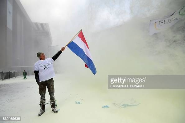 European Milk Board representative brandishes a Dutch flag as he stands in the middle of thrown milk powder in front of the European Council during a...