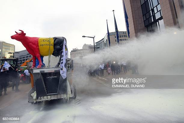 European Milk Board representatives spray milk powder in front of the European Council during a demonstration on the side of a meeting of EU...