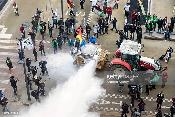 European Milk Board representatives spray milk powder in front of the European Council during a meeting of EU ministers of agriculture in Brussels...