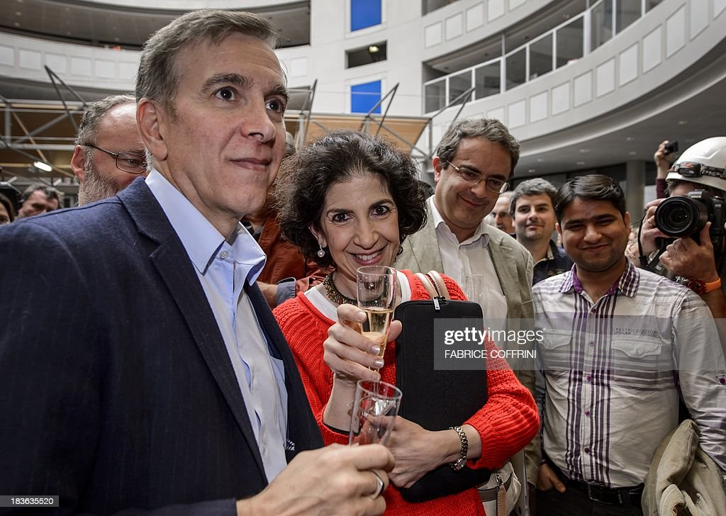 European Organisation for Nuclear Research (CERN) scientists CMS experiment spokesperson Joe Incandela (L) ATLAS's Fabiola Gianotti (2nd L) celebrate with champagne after the annoucement of the winners of the Nobel Prize for Physics on October 8, 2013 in Meyrin near Geneva. Peter Higgs of Britain and Francois Englert of Belgium won the Nobel Prize for Physics for conceiving of the so-called 'God particle' which confers mass. The presumed particle was discovered last year by Europe's mega-scale physics lab at CERN, near Geneva, after a decades-long search. COFFRINI