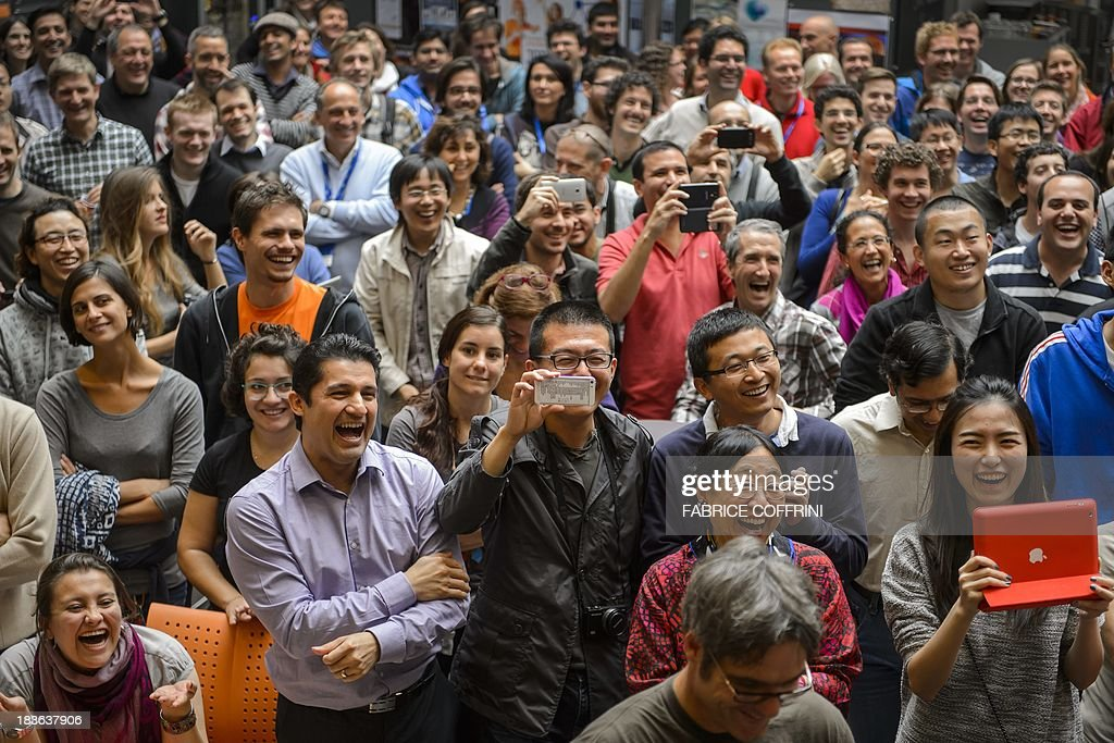 European Organisation for Nuclear Research (CERN) scientists reacts after the annoucement of the winners of the Nobel Prize for Physics on October 8, 2013 in Meyrin near Geneva. Peter Higgs of Britain and Francois Englert of Belgium won the Nobel Prize for Physics for conceiving of the so-called 'God particle' which confers mass. The presumed particle was discovered last year by Europe's mega-scale physics lab at CERN, near Geneva, after a decades-long search. COFFRINI