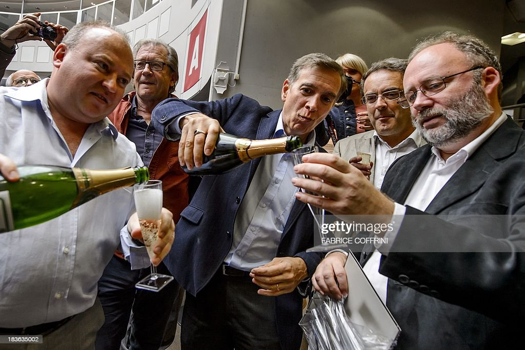 European Organisation for Nuclear Research (CERN) scientists with CMS experiment spokesperson Joe Incandela (3rd L) and Albert de Roeck (far R) celebrate with champagne after the annoucement of the winners of the Nobel Prize for Physics on October 8, 2013 in Meyrin near Geneva. Peter Higgs of Britain and Francois Englert of Belgium won the Nobel Prize for Physics for conceiving of the so-called 'God particle' which confers mass. The presumed particle was discovered last year by Europe's mega-scale physics lab at CERN, near Geneva, after a decades-long search. COFFRINI