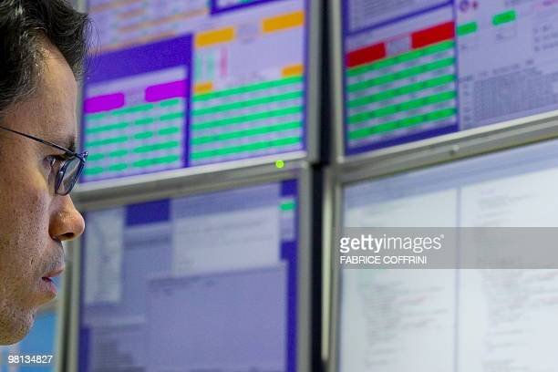 A European Organization for Nuclear Research scientist looks at a monitor in the Alice experiment control room on March 30 2010 near Geneva during an...