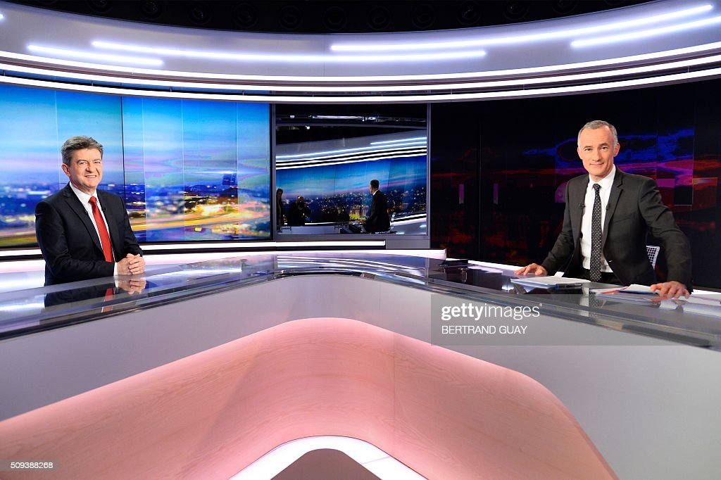 European parliament member and member of the leftist Parti de Gauche (PG) Jean-Luc Melenchon poses next to French journalist Gilles Bouleau before taking part in the broadcast news of French TV channel TF1 on February 10, 2016, in Boulogne, near Paris. / AFP / BERTRAND GUAY