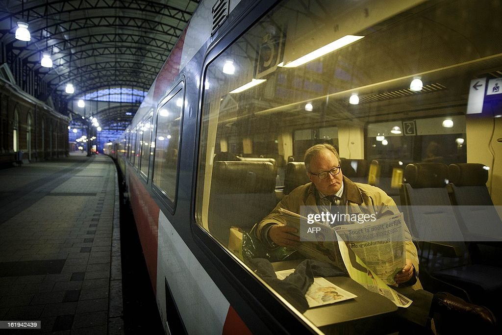 European parliament member Hans van Baalen reads a newspaper in the first direct train to Brussels from The Hague on February 18, 2013. As of today commuters can travel on the intercity train, operating twice daily,and which replaces the high-speed Fyra trains. The Fyra trains used between Amsterdam and Brussels are out of function since 17 January due to numerous problems culminating mid January with cancellations due to safety issues. AFP PHOPTO / ANP PHIL NIJHUIS netherlands out