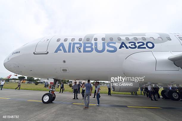 European plane manufacturer Airbus staff members look at the fist copy for test of the 200 mediumhaul Airbus A320neo passenger plane leaves its...