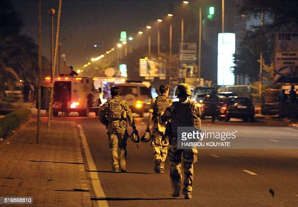 European soldiers walk in a street during an attack targeting a hotel hosting an EU military training mission in Bamako on March 21 2016 Four gunmen...