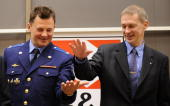 European Space Agency astronaut Frank De Winne of Belgium and Russian cosmonaut Roman Romanenko shake hands at a press conference outside Moscow in...