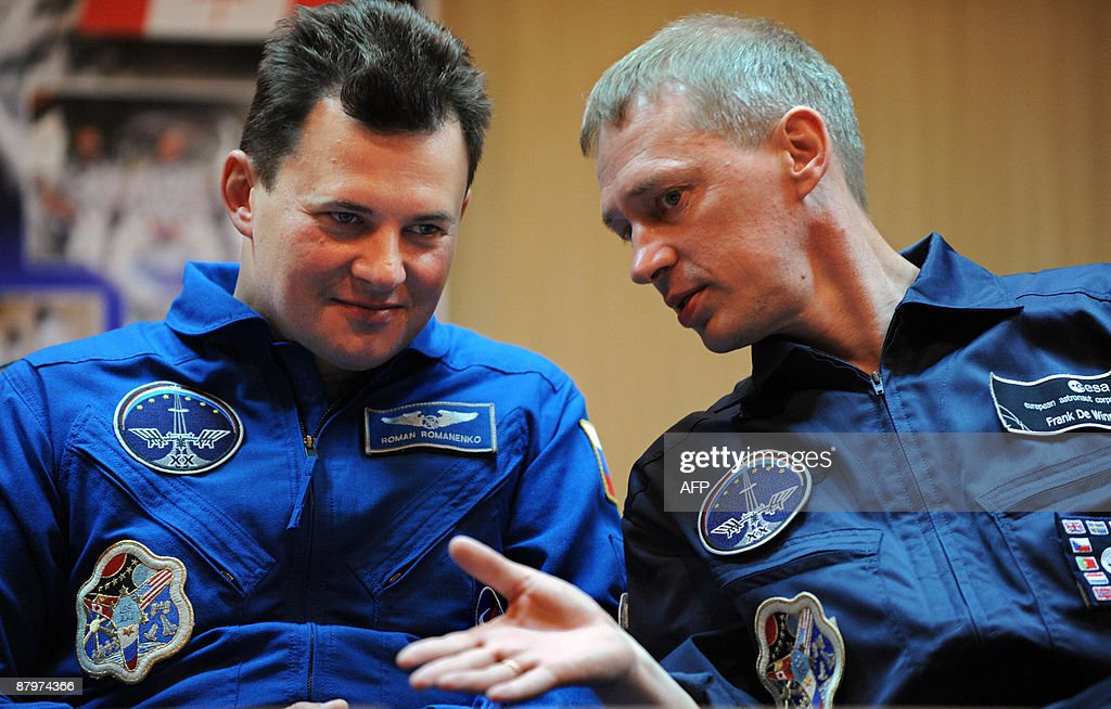 European Space Agency astronaut Frank De Winne of Belgium and Russian cosmonaut Roman Romanenko chat during a press conference at the Russian leased...
