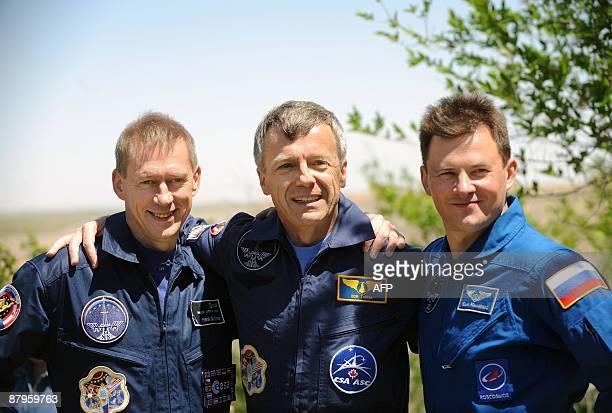 European Space Agency astronaut Frank De Winne of Belgium Canadian astronaut Robert Thirsk and Russian cosmonaut Roman Romanenko pose for the press...