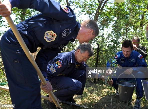 European Space Agency astronaut Frank De Winne of Belgium Canadian astronaut Robert Thirsk and Russian cosmonaut Roman Romanenko plant a tree at the...