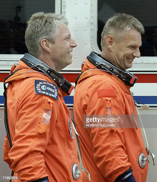 European Space Agency astronaut Thomas Reiter of Germany and mission specialist Piers Sellers walk to the bus that will take the space shuttle...