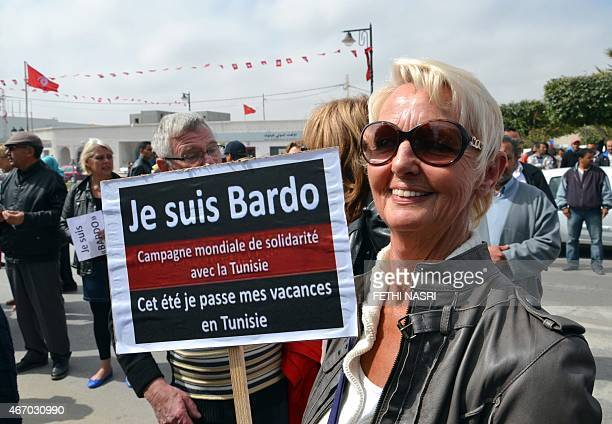 A European tourist holds a banner reading in French 'I am Bardo Global campaign of solidarity with Tunisia This summer I will spend my holiday in...