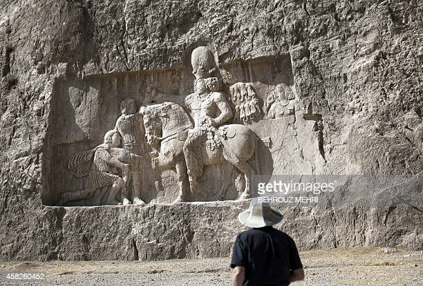 European tourist looks at the overlifesized rock relief triumph of Sassanid emperor Shapur I over the Roman Emperor Valerian and Philip the Arab at...