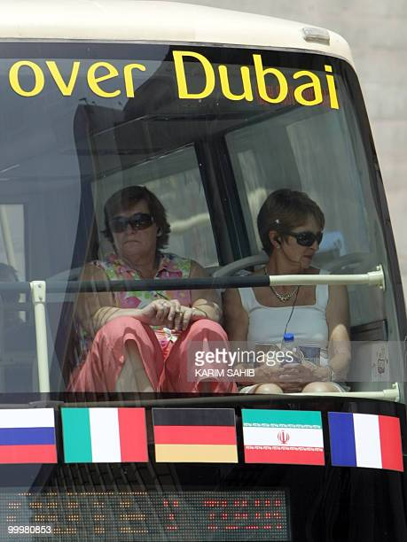 European tourists sit on May 19 2010 in a bus bearing the flag of the Islamic republic of Iran among other flags in the Gulf emirate of Dubai one of...