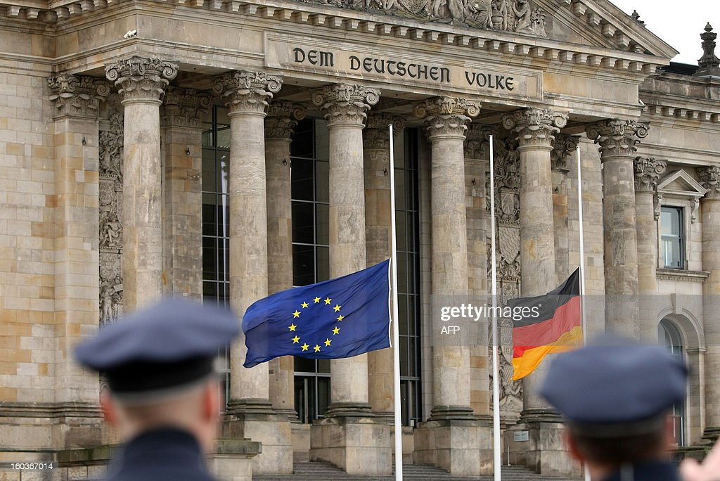 European Union (L) and German flags fly at half mast outside the Reichstag building, hosting the German lower house of Parliament Bundestag, in Berlin on January 30, 2013 prior to a memorial to be held by deputies for the victims of the Nazi regime, and the anniversary of the liberation of Auschwitz concentration camp on January 27, 1945. Since the date fell on a Sunday this year, the event was held later, on the day marking 80 years since Adolf Hitler became chancellor. BERRY