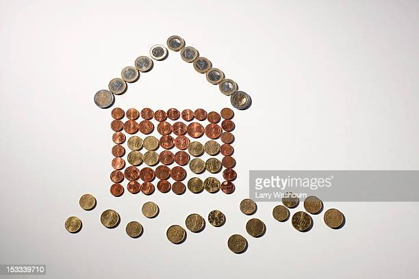 European Union coins arranged into the shape of house and grass