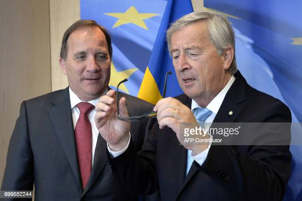 European Union Commission President JeanClaude Juncker looks at his glasses as he welcomes Swedish Prime Minister Stefan Lofven prior to a meeting at...