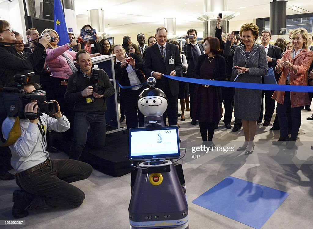 European Union Commissioner for Digital Agenda Neelie Kroes (2nd R) prepares to open the exhibition 'Made in Europe' after a robot brought her the scissors to cut the blue ribbon at the European Parliament in Brussels on October 8, 2012. AFP PHOTO / Thierry Charlier