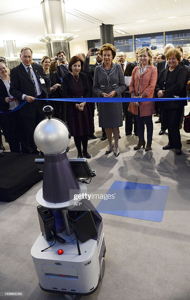 European Union Commissioner for Digital Agenda Neelie Kroes (3rd R) prepares to open the exhibition 'Made in Europe' as a robot brings her the scissors to cut the blue ribbon at the European Parliament in Brussels on October 8, 2012. AFP PHOTO / Thierry Charlier