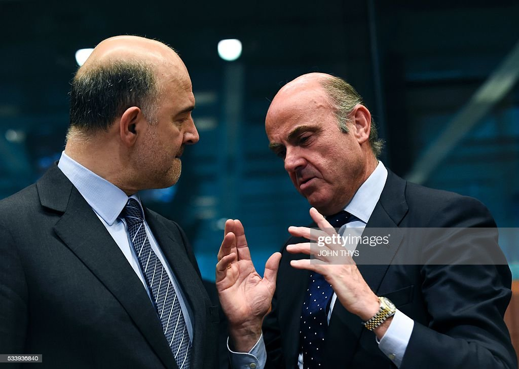 European Union Commissioner of Economic, Financial Affairs, Taxation and Customs Pierre Moscovici (L) listens to Spanish Economy Minister Cristobal Montoro Romero (R) during a Eurogroup meeting at the European Union headquarters in Brussels on May 24, 2016. Eurozone finance ministers said they hoped to unlock vital bailout cash for Greece on May 24, but warned of tough talks on debt relief that the IMF has demanded as the price for staying with the programme. / AFP / JOHN