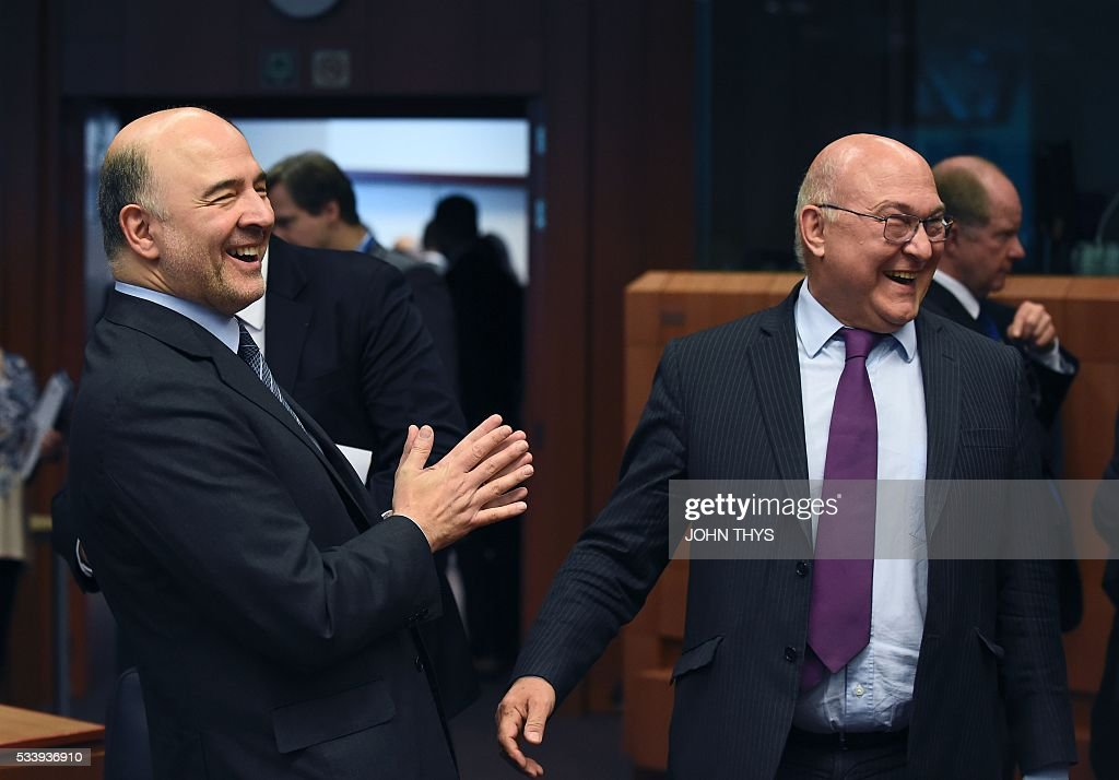 European Union Commissioner of Economic, Financial Affairs, Taxation and Customs Pierre Moscovici (L) laughs with France's Minister of Finance and Public Accounts Michel Sapin (R) during a Eurogroup meeting at the European Union headquarters in Brussels on May 24, 2016. Eurozone finance ministers said they hoped to unlock vital bailout cash for Greece on May 24, but warned of tough talks on debt relief that the IMF has demanded as the price for staying with the programme. / AFP / JOHN