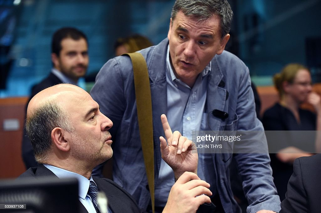 European Union Commissioner of Economic, Financial Affairs, Taxation and Customs Pierre Moscovici (L) talks with Greek Finance Minister Euclid Tsakalotos (R) during a Eurogroup meeting at the European Union headquarters in Brussels on May 24, 2016. Eurozone finance ministers said they hoped to unlock vital bailout cash for Greece on May 24, but warned of tough talks on debt relief that the IMF has demanded as the price for staying with the programme. / AFP / JOHN