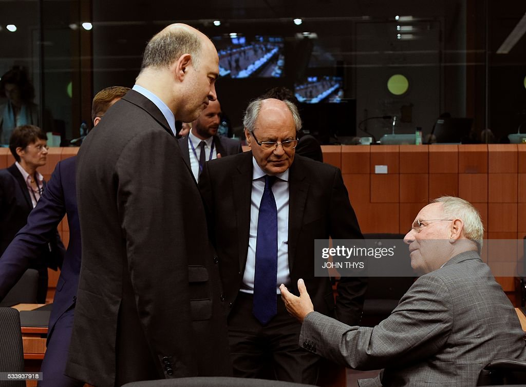 European Union Commissioner of Economic, Financial Affairs, Taxation and Customs Pierre Moscovici (L) talks with Maltese Finance Minister Edward Scicluna (C) and German Finance Minister Wolfgang Schaeuble (R) during a Eurogroup meeting at the European Union headquarters in Brussels on May 24, 2016. Eurozone finance ministers said they hoped to unlock vital bailout cash for Greece on May 24, but warned of tough talks on debt relief that the IMF has demanded as the price for staying with the programme. / AFP / JOHN