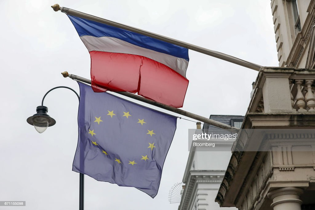 A European Union (EU) flag and a French flag fly outside the French consulate in London, U.K., on Friday, April 21, 2017. Three days before the first round of voting for their next president, a line snakes around a block in South Kensington, one of the most expensive and iconic neighborhoods in the city that also happens to be the epicenter of the French community -- home to its consulate, a school and various bistros and cafes that cater to the 300,000 French expats living in the U.K. Photographer: Chris Ratcliffe/Bloomberg via Getty Images