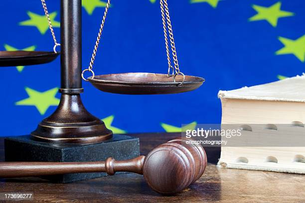 European union flag behind scales and wooden gavel
