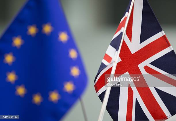A European Union flag left and a British Union Flag also know as a Union Jack stand at a foreign exchange brokerage in Tokyo Japan on Friday June 24...