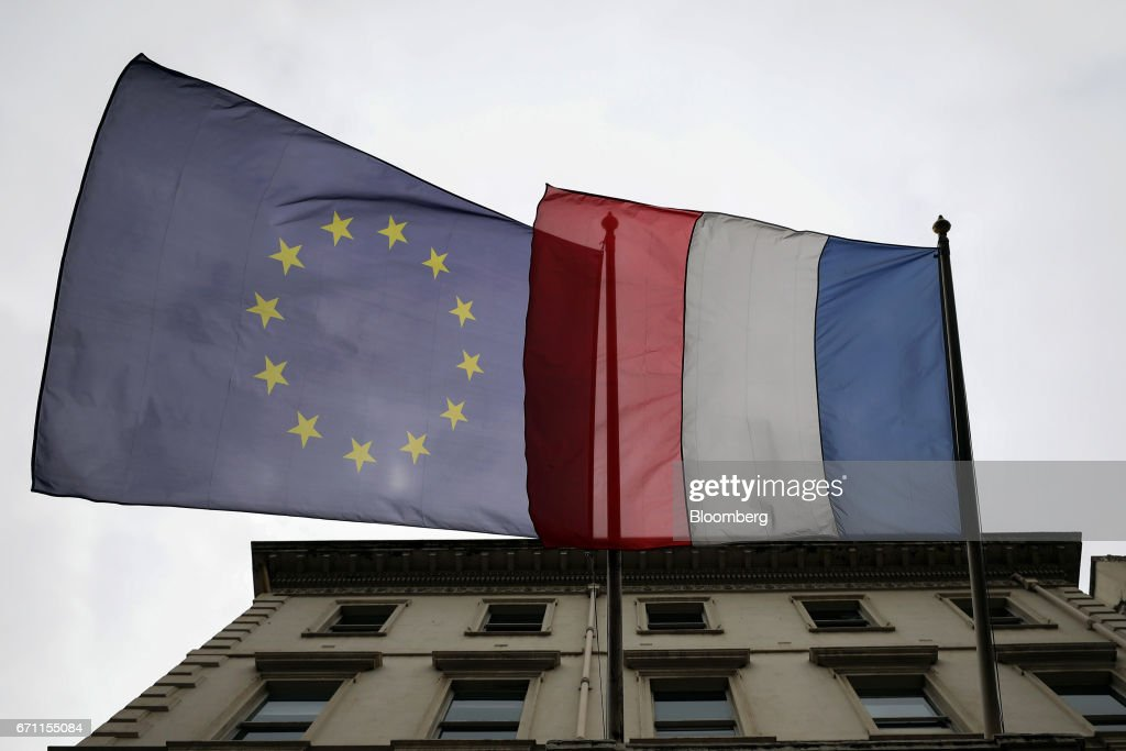 A European Union (EU) flag, left, and a French flag fly outside the French consulate in London, U.K., on Friday, April 21, 2017. Three days before the first round of voting for their next president, a line snakes around a block in South Kensington, one of the most expensive and iconic neighborhoods in the city that also happens to be the epicenter of the French community -- home to its consulate, a school and various bistros and cafes that cater to the 300,000 French expats living in the U.K. Photographer: Chris Ratcliffe/Bloomberg via Getty Images