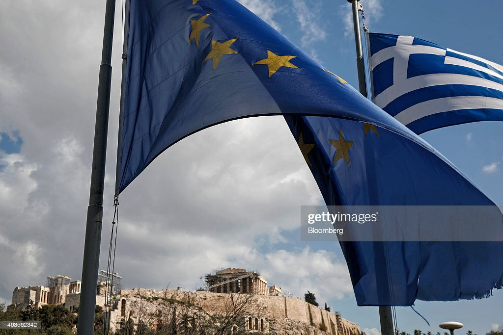 A European Union (EU) flag, left, flies alongside a Greek national flag beneath the Parthenon temple on Acropolis Hill in Athens, Greece, on Sunday, Feb. 15, 2015. Greece's euro-area creditors voiced skepticism that a breakthrough was within reach over financing Europe's most indebted state. Photographer: Yorgos Karahalis/Bloomberg via Getty Images