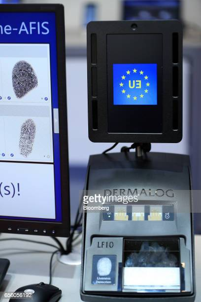 A European Union flag sits on the display screen beside a Dermalog LF10 biometric fingerprint scanner at the Dermalog Identification Systems GmbH...