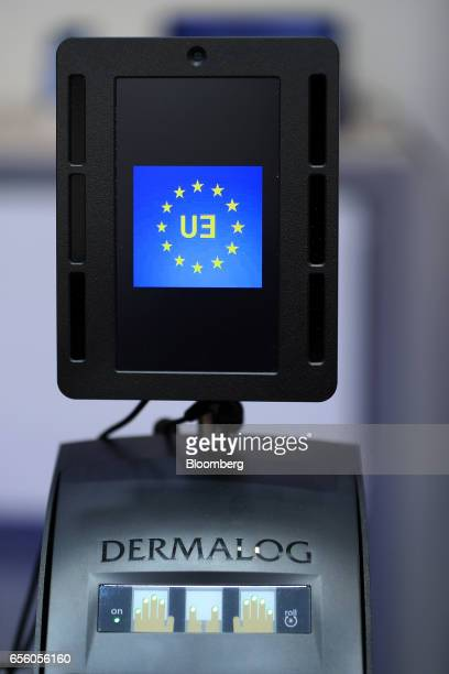 A European Union flag sits on the display screen of a Dermalog LF10 biometric fingerprint scanner at the Dermalog Identification Systems GmbH...