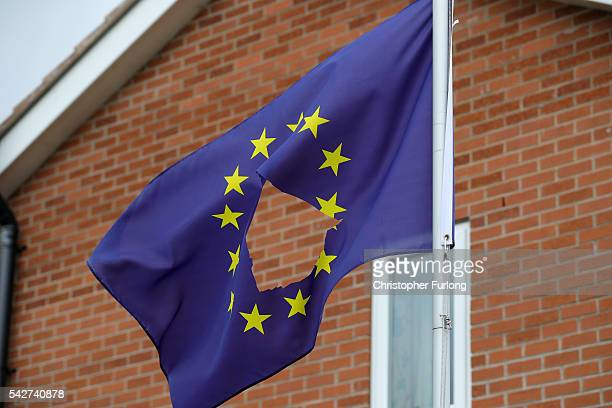 European Union flag with a hole cut in the middle flies at half mast outside a home in Knutsford Cheshire after today's historic referendum on June...